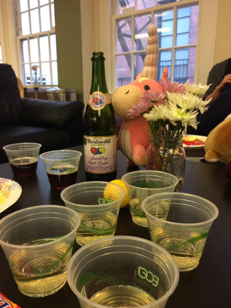 A stuffed balloonicorn and cups of champagne