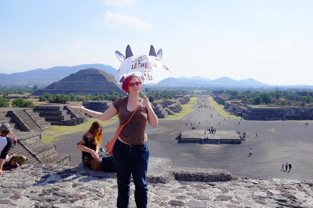 Breanne holds an umbrella with cow ears and horns in front of the pyramids of Teotihuacan